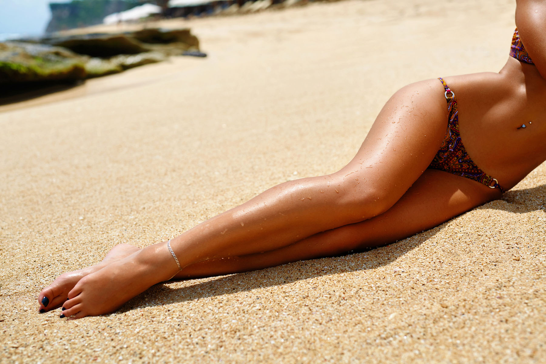 Sexy Long Woman Legs Sunbathing On Beach Sand. Body Part