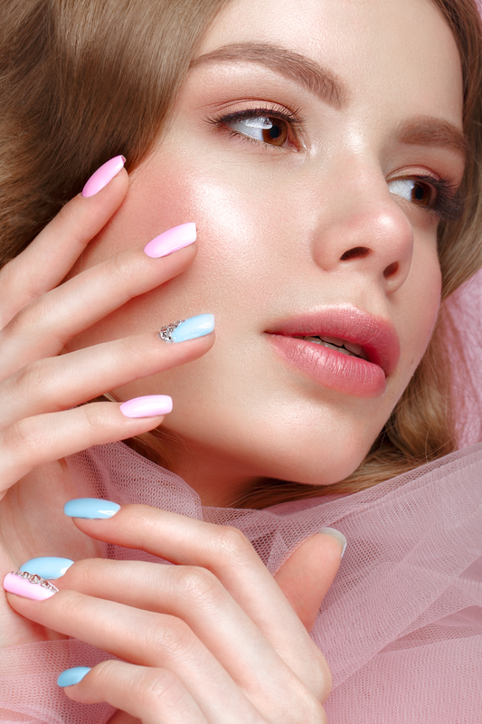 Beautiful girl with light make-up and gentle manicure in pink clothes. Beauty face. Design nails.